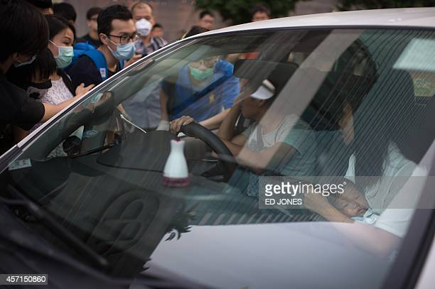 The driver of a car carrying a mother and baby talks to prodemocracy protesters before being allowed to pass through a road block in the Admiralty...