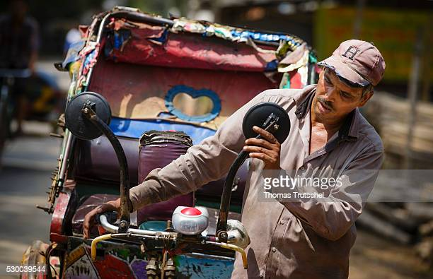 The driver of a rickshaw repaired his bike with a hammer in a workshop on April 13, 2016 in Savar, Bangladesh.