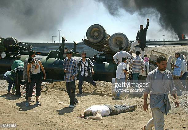 The driver of a US military tanker lies dead on the ground as Iraqi insurgents celebrate after attacking it with rocketpropelled grenade 09 April...