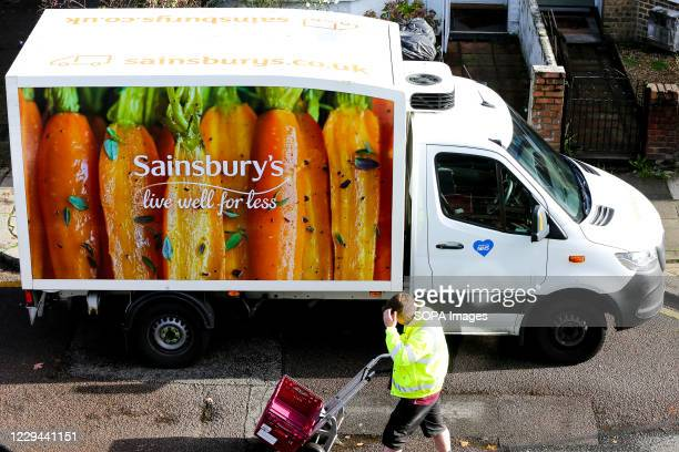 The driver of the Sainsbury's delivery van delivers the grocery delivery following an online order placed by the customer.