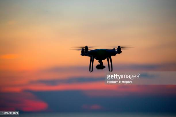 the drone in sunset sky. - drone stock pictures, royalty-free photos & images