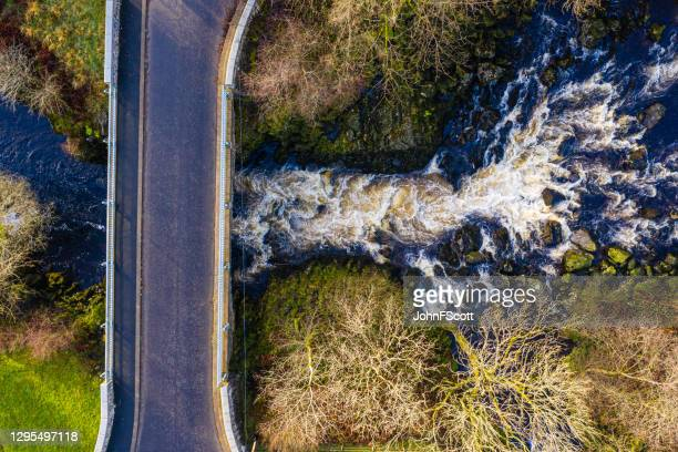 the drone view looking directly down onto a bridge crossing a narrow section of fast flowing water in dumfries and galloway south west scotland - tree stock pictures, royalty-free photos & images