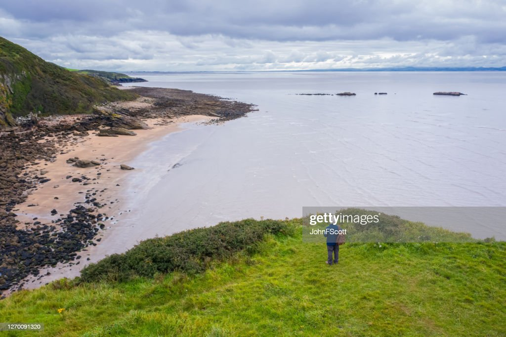The drone view of a senior man standing alone at the coast in Dumfries and Galloway, south west Scotland : Stock Photo