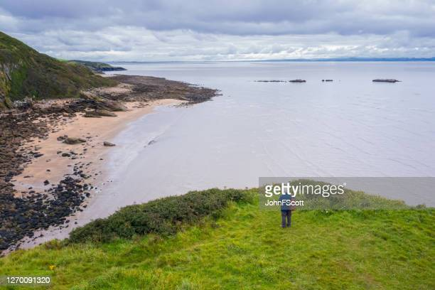 the drone view of a senior man standing alone at the coast in dumfries and galloway, south west scotland - dumfries and galloway stock pictures, royalty-free photos & images