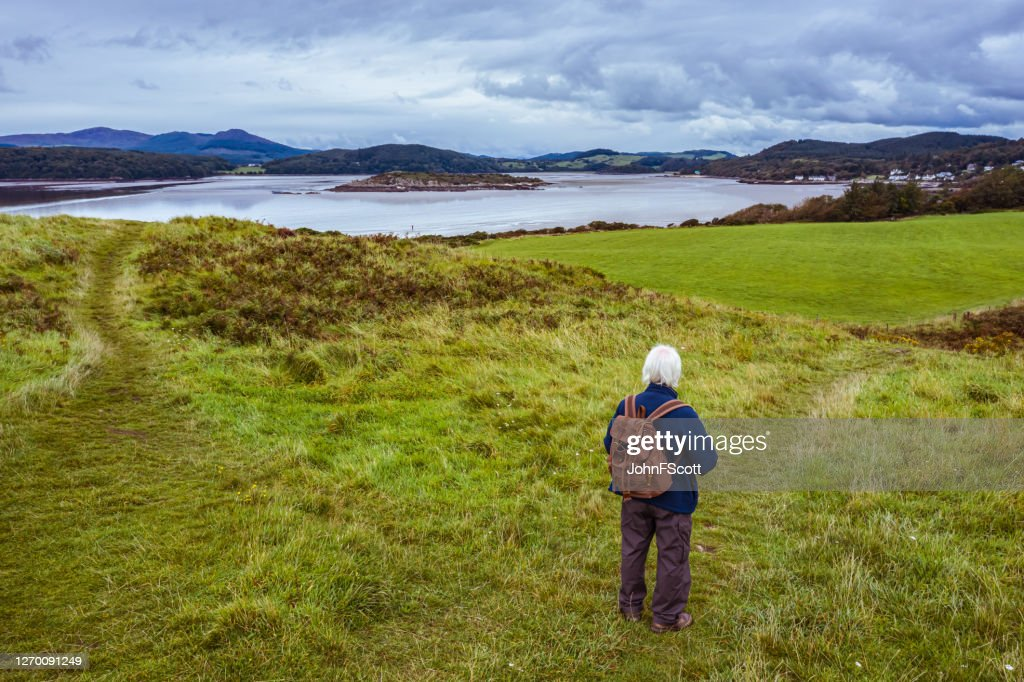 The drone view of a senior man standing alone on a path at the coast in Dumfries and Galloway, south west Scotland : Stock Photo
