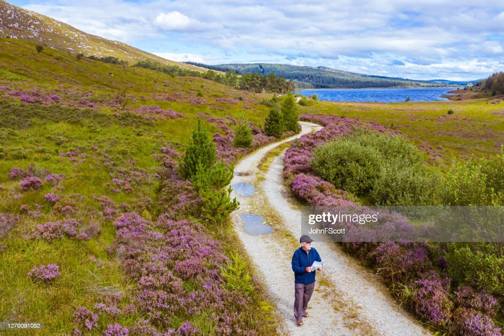 The drone view of an active senior man holding a map while standing on a dirt road in a remote part of Dumfries and Galloway, south west Scotland : Stock Photo