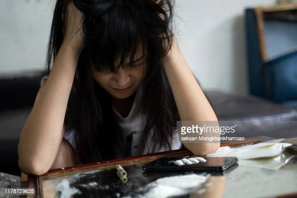 the drug addicts cry on the drug background. addicted women who have smeared makeup near the cocaine line, - drogati foto e immagini stock