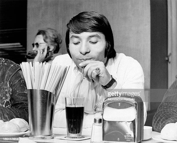 The drummer Alfio Cantarella member of the Italian music band Equipe 84 is enjoying his drink with a straw seated at a café in front of him a metal...