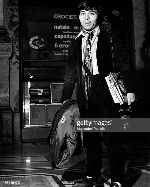The drummer of the Italian music band Equipe 84 Alfio Cantarella is ready to leave in his hands a coat and some books Italy 1968
