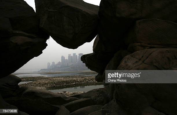 The dry riverbed of the low Yangtze River is dried out as the city skyline sits in the distance March 2 2007 in Chongqing Municipality China Six...