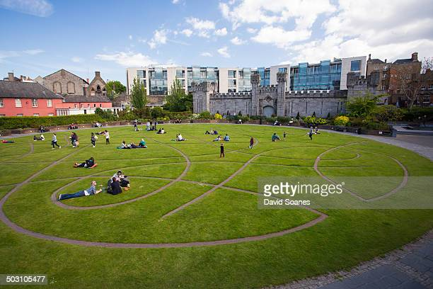 The Dubh Linn Gardens in the grounds of Dublin Castle, with people lying on the grass and enjoying the nice weather.