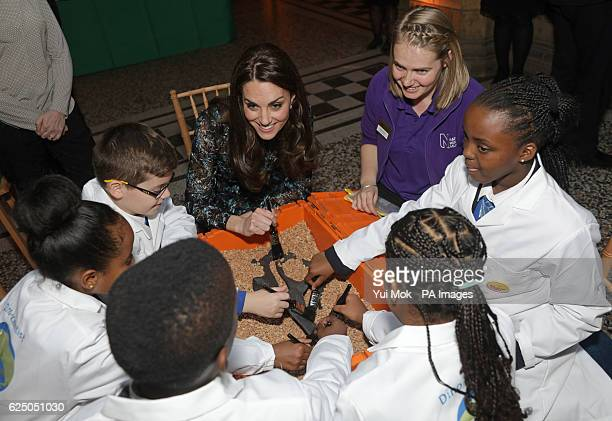 The Duchess of Cambridge examines a replica Diplodocus fossil as she attends a children's tea party with pupils from Oakington Manor Primary School...