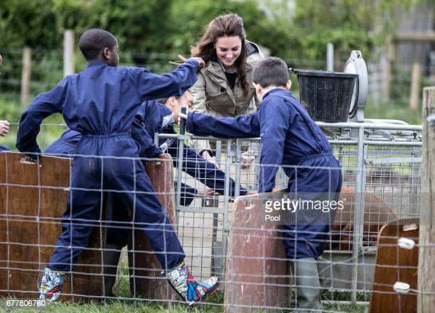 The Duchess of Cambridge holds a pig board as she helps children from Vauxhall primary school in London herd a pig into a pen to be weighed during a...