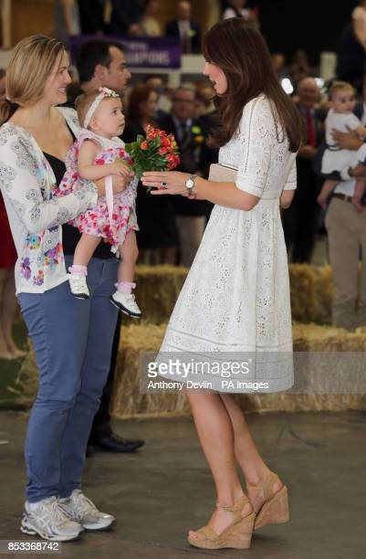 The Duchess of Cambridge receives flowers as the Duke and Duchess of Cambridge as they view agricultural stands at the Royal Easter Show at Sydney...