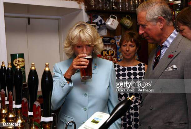 The Duchess of Cornwall tastes the Cambrian Heart beer that the Prince of Wales has just pulled in the bar of the Neuadd Arms Hotel Llanwrtyd Wells