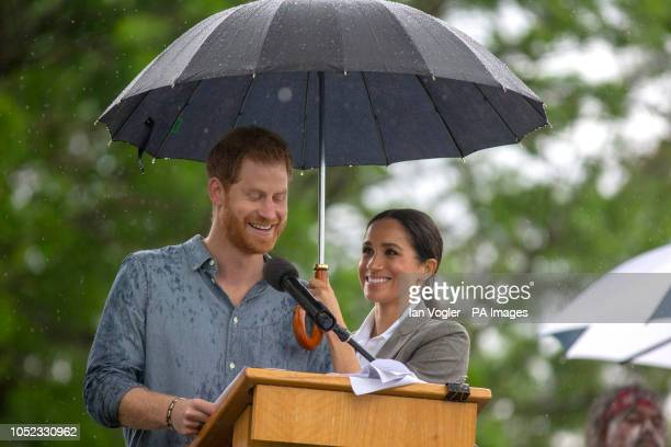 The Duchess of Sussex holds an umbrella as the Duke of Sussex makes a speech at a community picnic in Victoria Park in Dubbo, New South Wales, on the...