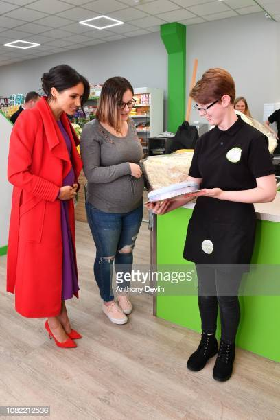 The Duchess of Sussex presents member Angela Midgley with a cake held by member of staff Kate Phillips as the Duke and Duchess of Sussex officially...