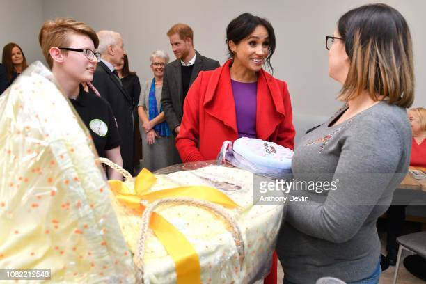 The Duchess of Sussex presents member Angela Midgley with a moses basket as the Duke and Duchess of Sussex officially open Number 7 a Feeding...