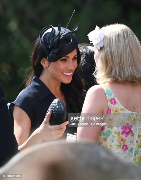 The Duchess of Sussex talks to fellow guests as they arrive to attend the wedding of Charlie van Straubenzee and Daisy Jenks at St Mary the Virgin...