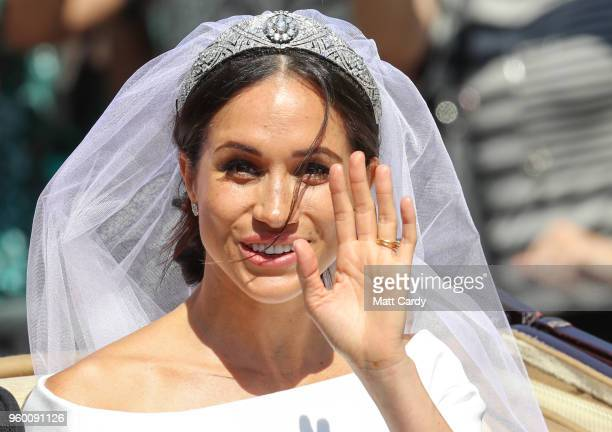 The Duchess of Sussex waves from the Ascot Landau carriage during the procession after their marriage St George's Chapel on May 19, 2018 in Windsor,...