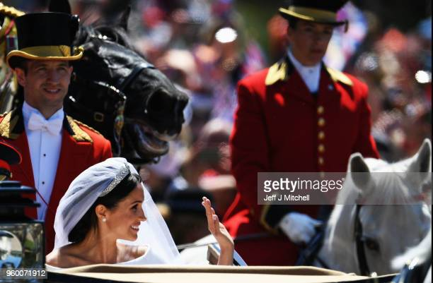 The Duchess of Sussex waves in the Ascot Landau carriage during the procession on The Long Walk after getting married to Prince Harry Duke of Sussex...