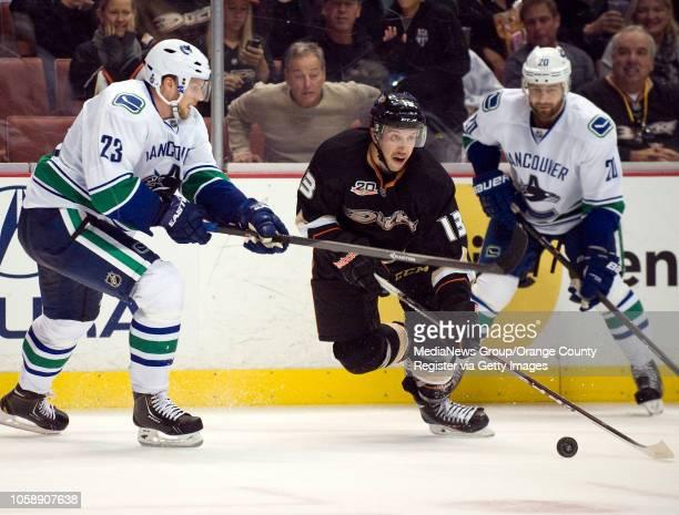 The Ducks' Nick Bonino gets past the Canucks' Alexander Edler left and Chris Higgins at Honda Center in Anaheim on November 10 2013