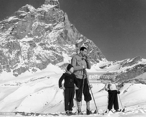 The Duke Amedeo of Savoy standing on the ski slopes with two children 1930s