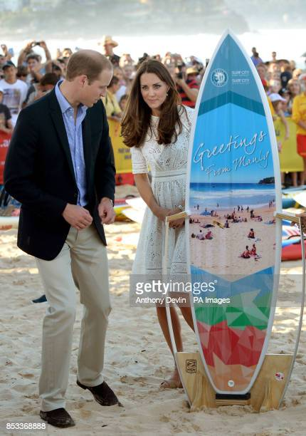 The Duke and Duchess of Cambridge are presented with a surf board as they view a surf lifesaving display and meet volunteers at Manly Beach Sydney...
