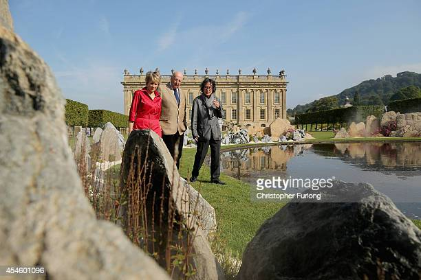 The Duke and Duchess of Devonshire and artist Xu Bing view his work Tao Huan Yuan A lost village Utopia in front of Chatsworth House which is part of...