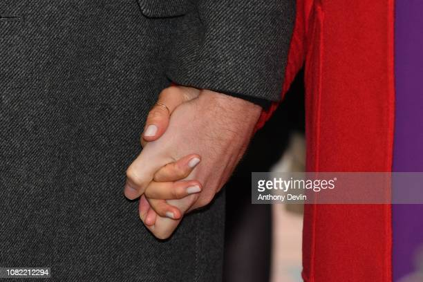 The Duke and Duchess of Sussex hold hands as they officially open Number 7 a Feeding Birkenhead citizens supermarket and community cafe on January 14...
