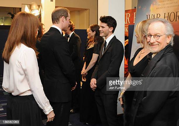 The Duke of Cambridge speaks with actor Jeremy Irvine as director Steven Spielberg looks on as they attend the 'War Horse' UK film premiere at the...