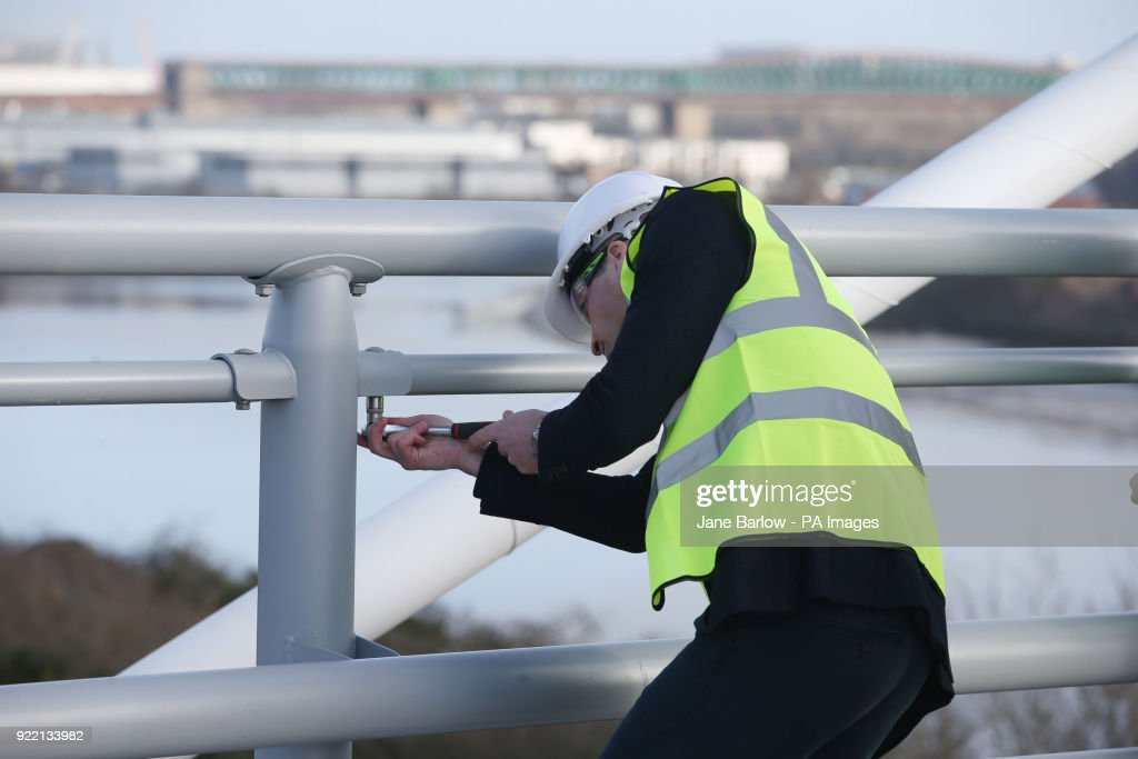 The Duke of Cambridge wear a safety helmet and high visibility vest as he attaches a bolt during a visit to the Northern Spire bridge across the River Wear in Sunderland.