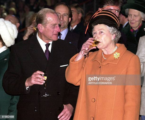 The Duke of Edinburgh and British Queen Elizabeth II toast the new millennium 31 December 1999 during celebrations at the Millennium Dome in London
