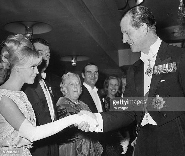 The Duke of Edinburgh attending the Royal Film Performance in London shakes hands with Swedish actress Britt Ekland The Royal Film Performance of the...
