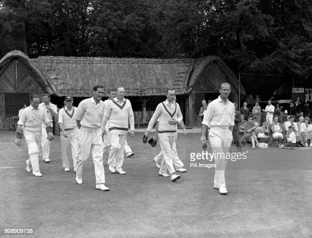 The Duke of Edinburgh leads his team out to field in a cricket match against a side captained by Lord Porchester The event was in aid of the National...