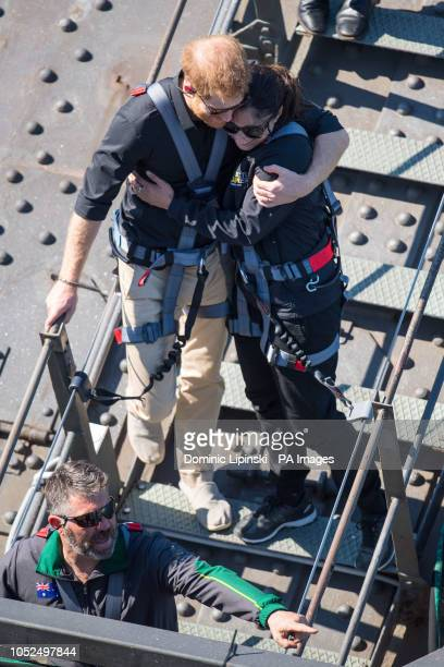 The Duke of Sussex hugs a fellow climber during a visit to the Sydney Harbour Bridge with Prime Minister of Australia Scott Morrison and Invictus...
