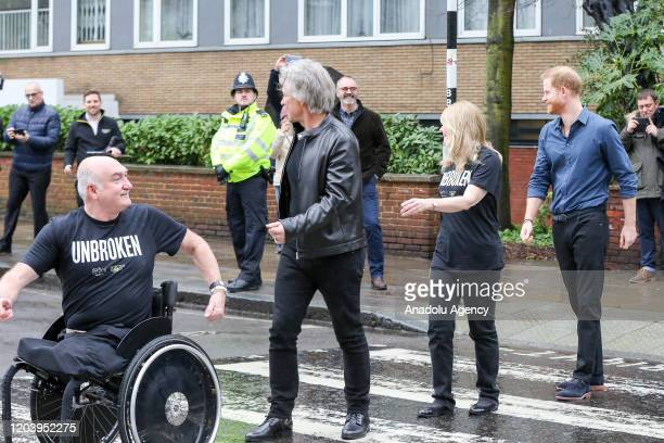 The Duke of Sussex Jon Bon Jovi an American singersongwriter and members of the Invictus Games Choir pose for the photographs at the crossing outside...