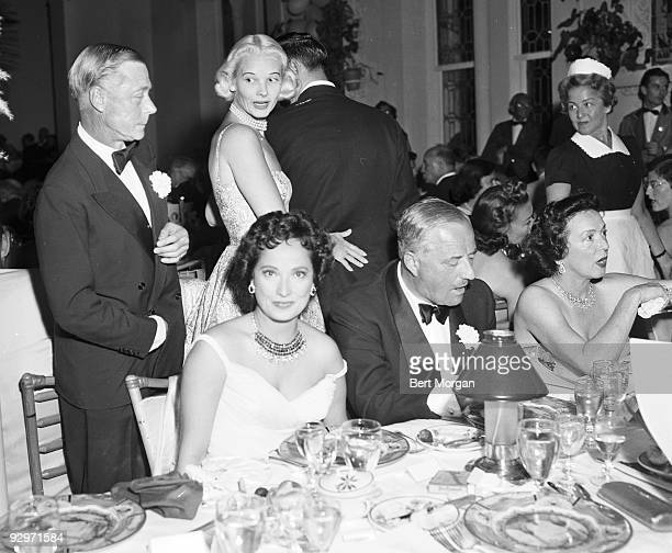 The Duke of Windsor and CZ Guest standing while Merle Oberon and Mrs Stephen Sanford are seated at a table at the Polo Ball La Coquille restaurant...