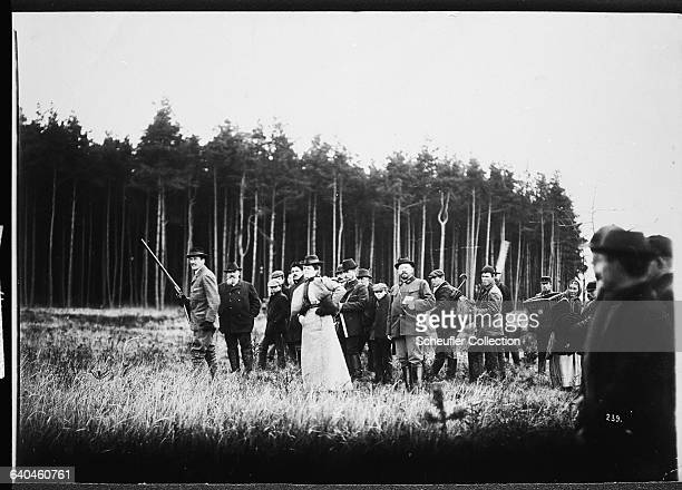 The Duke of Wurtenberg stands in a woodland clearing with a shooting party The Duke holds a gun | Location Konopiste Czech Lands