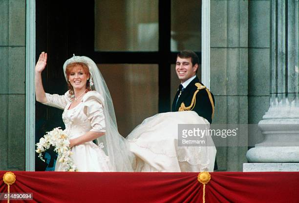 The Duke of York Andrew carries Duchess Sarah Ferguson's train as she waves from the balcony on their wedding day