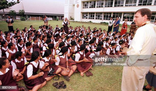 The Duke of York wearing a flower garland listens to a group of school singers during a visit to the High school in Tonga this morning The Duke is...