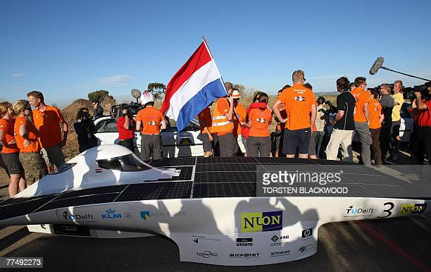 The Dutch Nuon Solar Team jubilate after their car, Nuna 4, crossed the official finish line to win their fourth consecutive World Solar Challenge in...