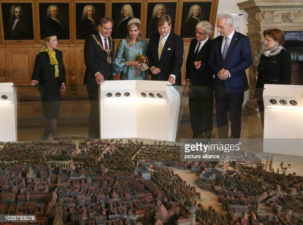 The Dutch royal couple WillemAlexander and Maxima write look at a model of the city in the OldTown Hall in Leipzig Germany 09 February 2017 Standing...