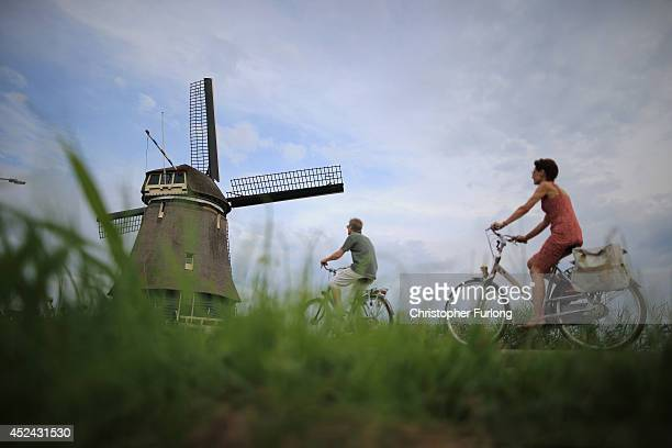 The Dutch try to continue with daily life as people cycle past a windmill in the traditional Dutch town of Volendam and the Netherlands tries to come...