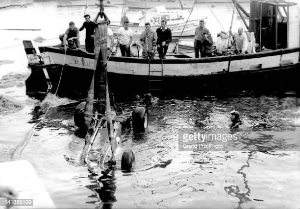 The DW Racing Enterprises Lotus 33 Climax V8 of Paul Hawkins of Australia is recovered from the harbour after crashing on lap 79 during the Monaco...
