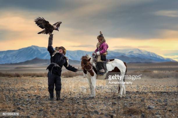 The eagle hunter's siblings coaching their eagle.