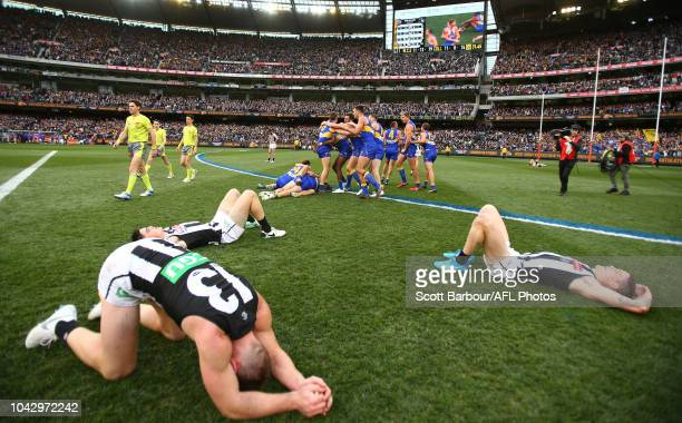 The Eagles celebrate victory at the final siren as Magpies players look dejected during the 2018 AFL Grand Final match between the Collingwood...