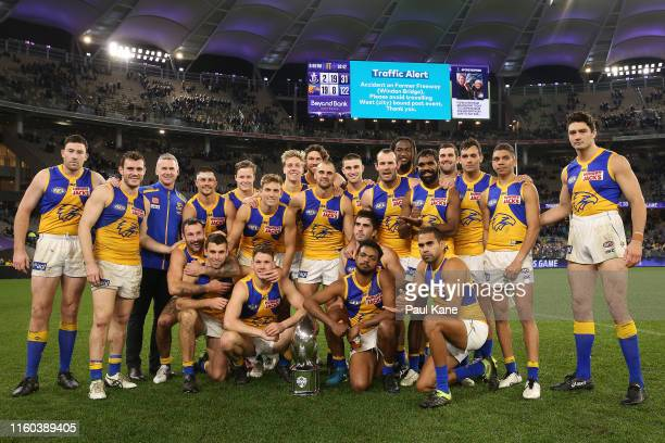 The Eagles pose with the RAC Western Derby trophy after winning the round 16 AFL match between the Fremantle Dockers and the West Coast Eagles at...
