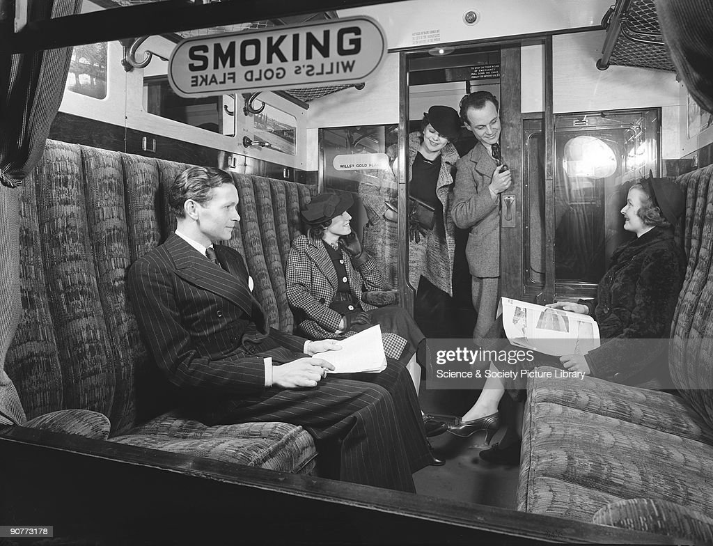 Passengers in a first class railway carriage smoking compartment, 1936. : News Photo