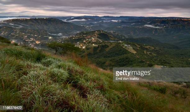 the early morning lights that twinkle on the monteseel landscape with a thick cumulus cloud cover above the valley. inchanga, durban. kwazulu-natal, south africa - durban stock pictures, royalty-free photos & images